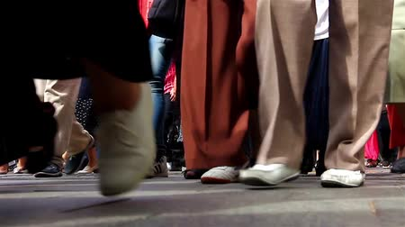 baixo : The feet of dozens of pedestrians walking on the sidewalk