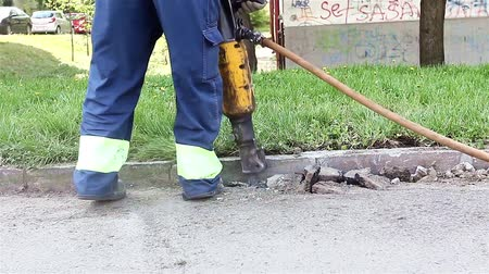 работник физического труда : Construction worker is using Jack Hammer and breaking street asphalt