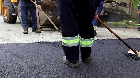мощение : Workers collecting excess tarmac in Earth Mover machine during road street repairing activity