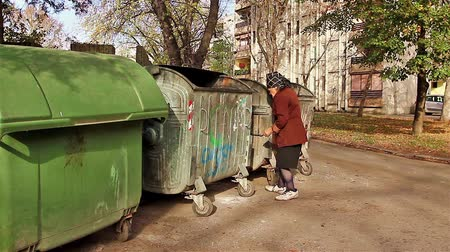 atık : Homeless woman is searching for food in garbage container.