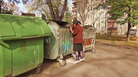 atık :  Woman in poverty is searching something in garbage container.