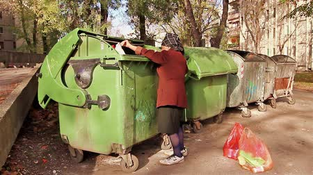 yoksulluk : Woman in poverty is searching something in garbage container. Stok Video