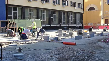 ajoelhado : Workers stack paving slabs on city streets Vídeos