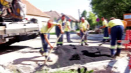 road construction : Road Construction in blurred view. Hot asphalt is applied to the street by construction crew.