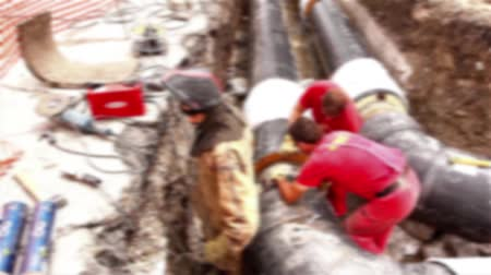 rurociąg : Blurred view on team of workers until assembly a new pipeline.