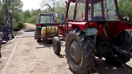 bóia : Ferry boat for transport agricultural machinery across the river Tractor with attached agricultural sprayer is leaving from ferry boat on shore