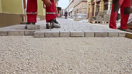 parke taşı : Masons hands are fitting flagstone. Close up view of construction workers hands until hes paving street.