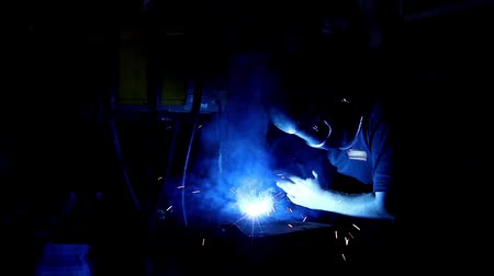 spawanie : Arc welder with welding sparks. Flashes and lot of sparks from welding work at dark in workshop.