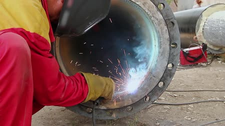 flange : Welder is welding flange to the pipe. Detail in welding of metalworker until he working on a pipeline.