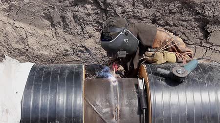 spawanie : Manual Metal Arc welding. Welder is welding pipeline to assemble two long pipes.