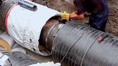 boru hattı : Preparing for next weld. Metal worker is grinding weld on new pipeline heating system.