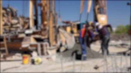 fogged : Blurred view construction site. Workers with shovels are throwing dry concrete mix in basket to lift up. Stock Footage