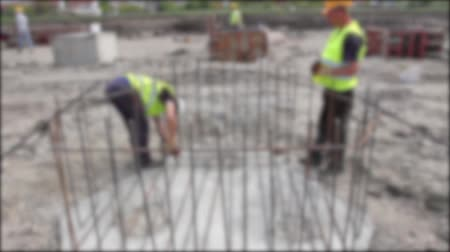 fogged : Rebar tying. Blurred view on workers until they are placing the rebar making a newly constructed footing frame.
