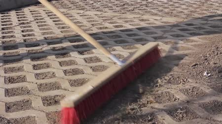 besom : Worker is cleaning new parking place with red broom. Worker sweeps urban space with a wide broom, brush cleaning. Stock Footage