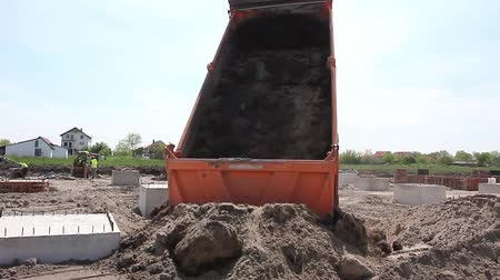 guba : Dump truck is unloading soil. Dumper truck is unloading soil or sand at construction site. Stock mozgókép