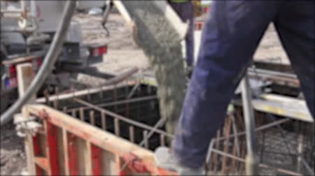 fogged : Blurred view at pouring concrete in reinforced mold. Workers at building site are pouring concrete in armored cage frame.