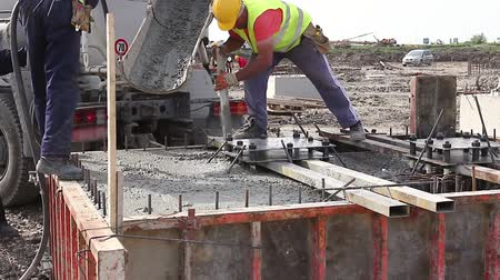гражданский : Pouring reinforced concrete. Workers at building site are pouring concrete in armored cage frame.