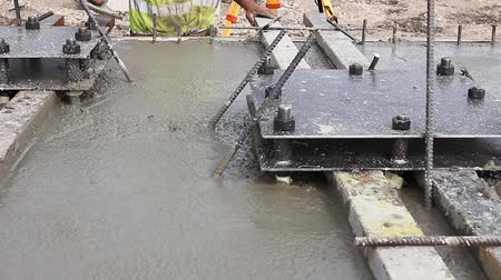 dengeleme : Concrete is leveling after pouring. Mason is using a trowel to finish top of the concrete foundation.