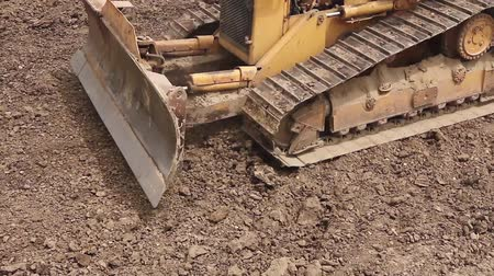 lagarta : Bulldozer machine is leveling construction site. Earthmover with caterpillar is moving earth outdoors. Stock Footage