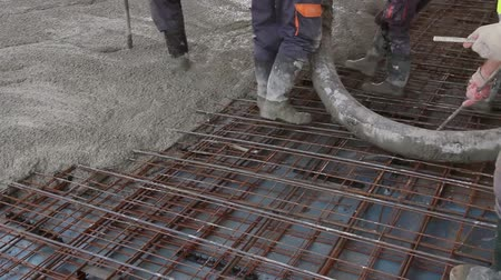 cement floor : Workers are spreading concrete on the construction site. Construction workers are pouring concrete in building foundation, directing pump tube on the right direction. Stock Footage
