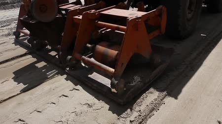 road construction : Close of plate compactor mounted on truck. Plate compactor is mounted to the truck, compacting sand at road construction site. Stock Footage