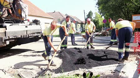 dengeleme : Zrenjanin, Vojvodina, Serbia - August 19, 2014: Mason is using a trowel tool to finish surface of the tarmac, asphalt. Stok Video