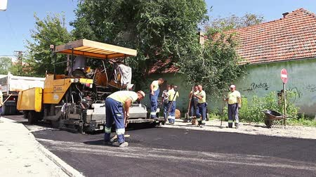 dengeleme : Zrenjanin, Vojvodina, Serbia - August 19, 2014: Hot asphalt is applied to the street with construction machinery.