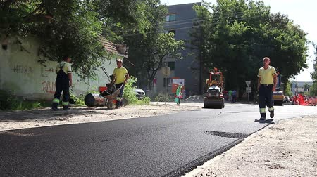 dengeleme : Zrenjanin, Vojvodina, Serbia - August 19, 2014: Hot asphalt is spreading with steamrollers during road works.