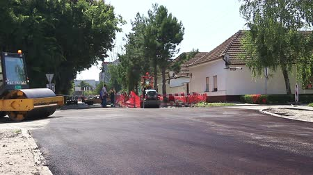 dengeleme : Zrenjanin, Vojvodina, Serbia - August 19, 2014: Two steamrollers are spreading, flatting hot asphalt. Hot asphalt is spreading with steamrollers during road works.