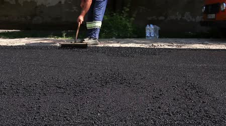 dengeleme : Worker is leveling manually hot asphalt during road works Worker is leveling tarmac using a trowel to finish asphalt. Stok Video