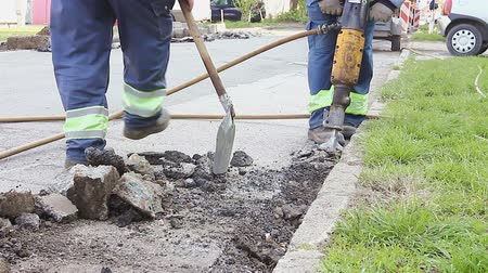 remover : Worker with a shovel collects broken asphalt behind jackhammer Labor with a shovel collects broken asphalt after another construction worker is using jackhammer.
