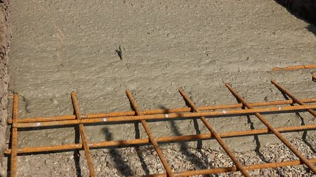átfedés : Concrete is flowing over reinforcement at the base of new building.