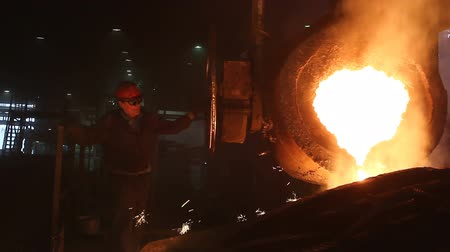 discharging : Discharge molten steel pouring from ladle Worker is turning hoop wheel to discharge molten steel from ladle into the mold for casting. Stock Footage