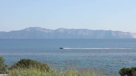 computação gráfica : Small boat is passing over sea. Coastline with mountain islands in backdrop.