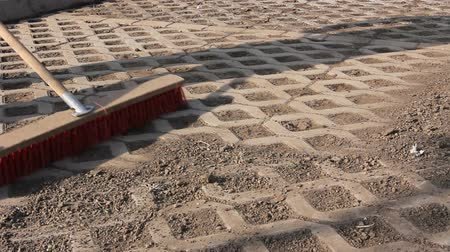 dry zone : Worker is cleaning modern cobblestone with red broom  Worker sweeps dry filth with a wide broom, brush cleaning paved urban space. Stock Footage