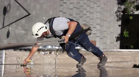 titular : Time lapse of above view on young man, industrial climber at work, he is washing building facade. Stock Footage