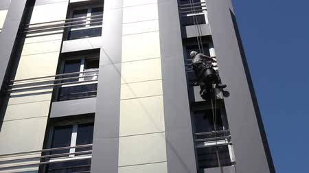 riskli : View from below on young man, industrial climber at work, he washing building facade. Stok Video