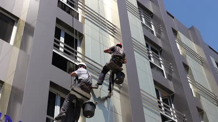 work at height : Two industrial climbers are washing, cleaning facade of a modern office building