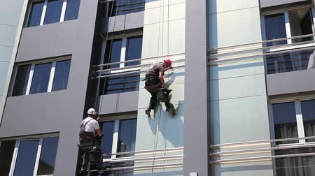 riskli : Two industrial climbers are washing, cleaning facade of a modern office building