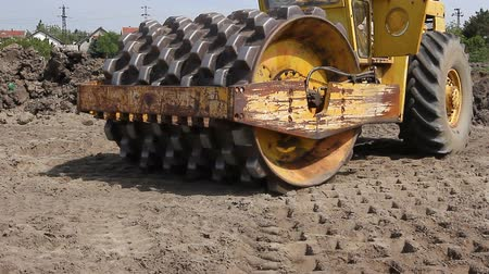 rulolar : Huge road roller with spikes is compacting soil at construction site.