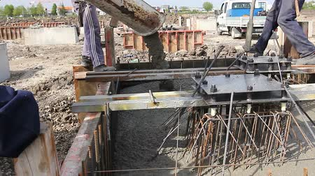 reinforced concrete : Pouring reinforced concrete in foundation mold Workers at building site are pouring concrete in mold from mixer truck.