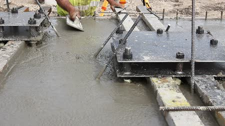 reinforced concrete : Worker is leveling concrete after pouring Mason is using a trowel to finish top of the concrete foundation. Stock Footage