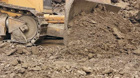 earthworks : Heavy earthmover, bulldozer machine is leveling construction site View on bulldozer, crawler while he is moving and leveling ground at building site. Stock Footage