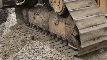 earthworks : Crawlers tracks, bulldozer machine is leveling construction site Close up view on bulldozers undercarriage during pushing ground at construction site. Stock Footage