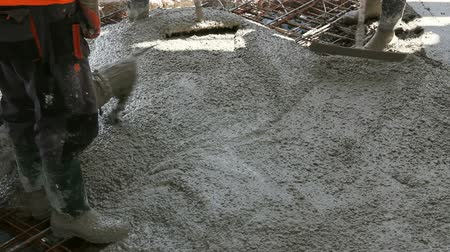 truss : Workers are spreading concrete over big reinforced floor on the construction site Construction workers are pouring concrete in building foundation, directing pump tube on the right direction. Stock Footage