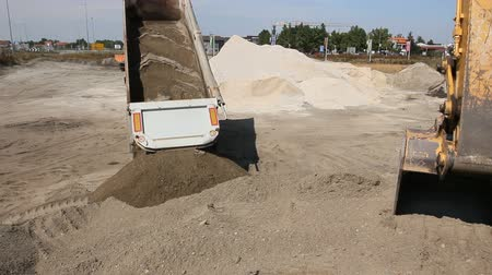 camionagem : Dumper truck is unload soil Dumper truck is unloading sand in excavator range at construction site.