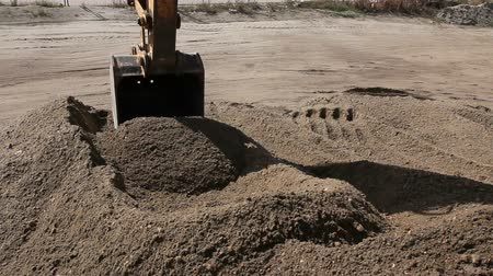 crawler : Excavator is preparing pile of sand for loading in truck on building site Yellow excavator is making pile of soil by pulling ground up on heap at construction site, project in progress. Stock Footage