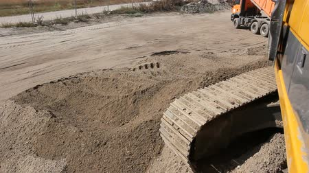 tracked : Excavator is preparing pile of sand for loading in truck on building site Yellow excavator is making pile of soil by pulling ground up on heap at construction site, project in progress. Stock Footage