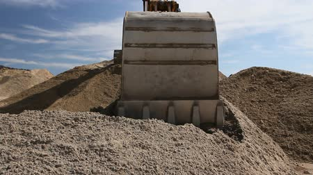 backhoe loader : Excavator is preparing pile of sand for loading in truck on building site Yellow excavator is making pile of soil by pulling ground up on heap at construction site, project in progress. Stock Footage