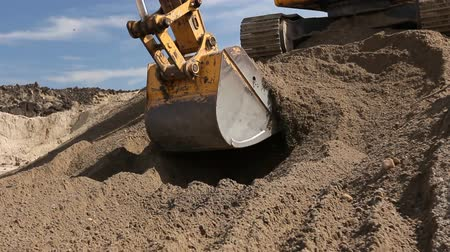 piled up : Excavator is preparing pile of sand for loading in truck on building site Yellow excavator is making pile of soil by pulling ground up on heap at construction site, project in progress. Stock Footage